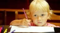Portrait of little girl drawing pencils on paper video