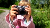 Portrait of little girl with photo camera in park video