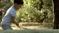 SLOW MOTION: Portrait of little golfer beats a golf ball video