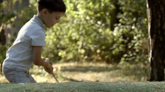 SLOW MOTION: Portrait of little golfer beats a golf ball video