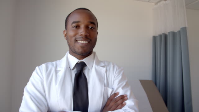Portrait Of Male Doctor Wearing White Coat In Exam Room video