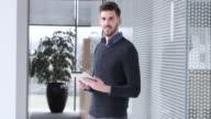 LD Portrait of male employee using tablet in hallway video