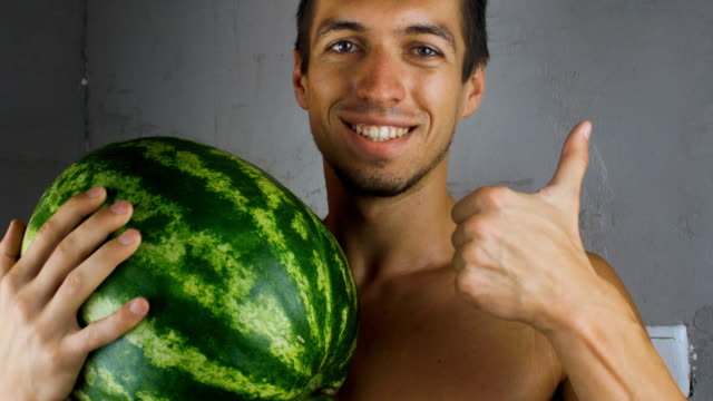portrait of man holding a watermelon in his hands video