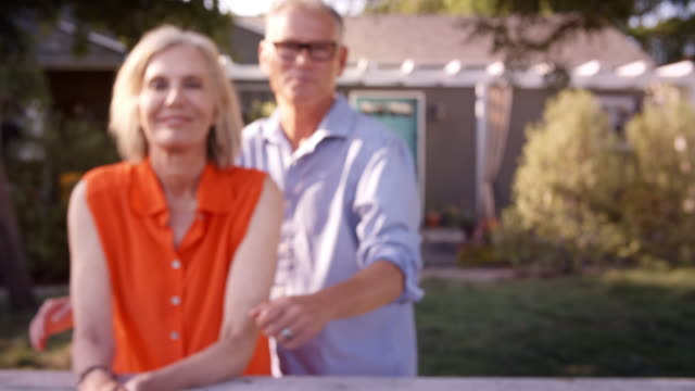 Portrait Of Mature Couple Looking Over Back Yard Fence video