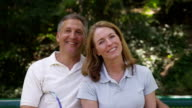 Portrait of mature couple outdoors with tennis racquets video