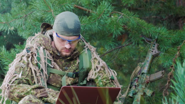 Portrait of military man sitting in the woods, dressed in camouflage. It uses laptop video