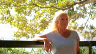 Portrait of modern attractive happy mature woman in sunlight video