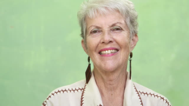 Portrait of old caucasian lady looking and smiling at camera video