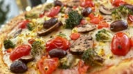 SLO MO Portrait of pizza with broccoli and mushrooms video