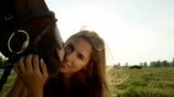 CLOSE UP: Portrait of pretty brunette girl kissing cute horse's muzzle video