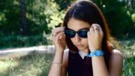 portrait of pretty Caucasian girl wears sunglasses in slow motion video
