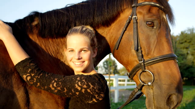 CLOSE UP: Portrait of pretty smiling girl embracing her brown horse on sunny day video