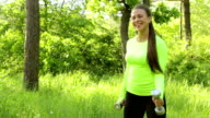 Portrait of pretty young girl doing exercise with dumbbell in park video