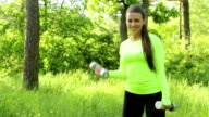 Portrait of pretty young girl doing exercise with dumbbell outdoors video