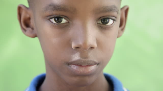 Portrait of sad young black boy looking at camera video