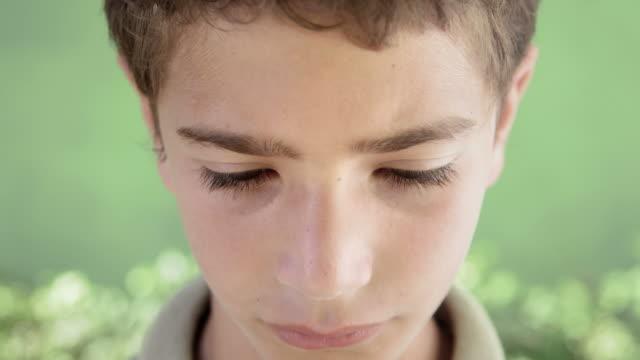 Portrait of sad young hispanic kid looking at camera video