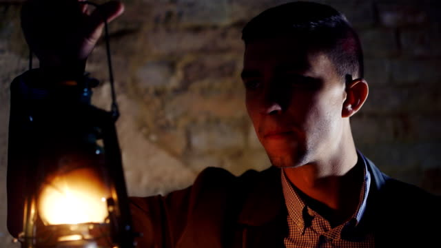 Portrait of scared businessman with a kerosene lamp. Concept - lost in the sea of business video