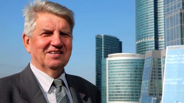 portrait of senior man against skyscrapers construction video