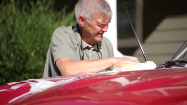 Portrait of senior man polishing car video