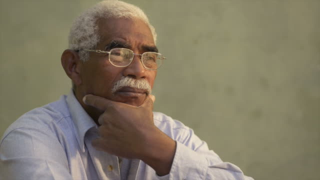 Portrait of serious african american old man looking away video