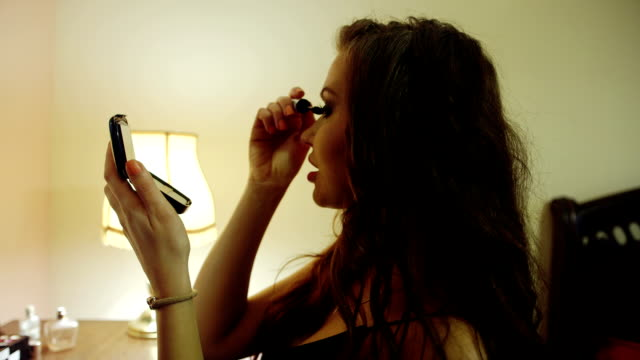 Portrait of sexy young girl in underskirt doing make up in her bedroom. video