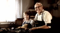 HD DOLLY: Portrait Of Shoemaker With Young Apprentice video