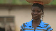 Portrait of smiling african woman carrying water on her head video