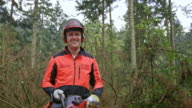 SLO MO Portrait of smiling logger standing on fallen tree video