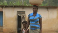 Portrait of smiling mother while carrying water on her head video