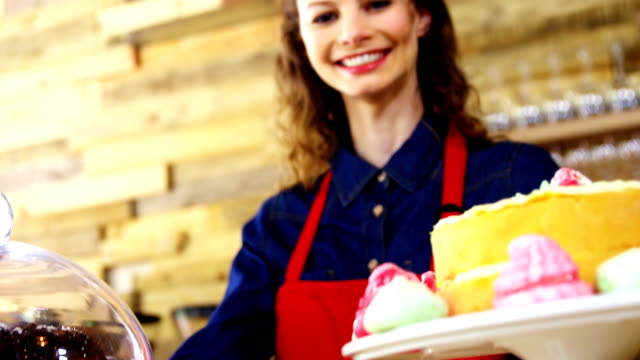 Portrait of smiling waitress holding cake at counter video