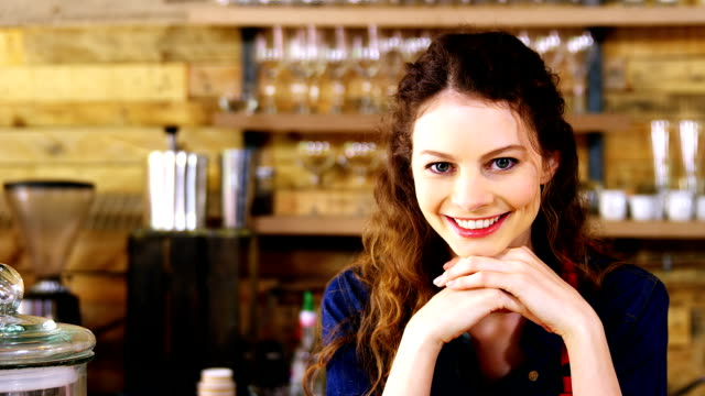 Portrait of smiling waitress leaning at counter video