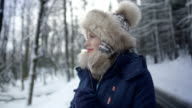 Portrait of smiling woman enjoying winter in a snowy forest. video