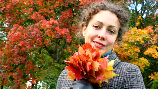Portrait of smiling young woman with autumn leaves in park video