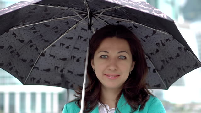 Portrait of stylish woman standing with umbrella video