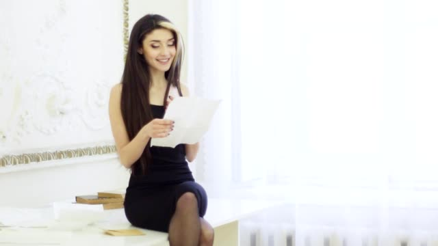Portrait of stylish young woman with brown hairs reading letter in apartment sitting on the table video