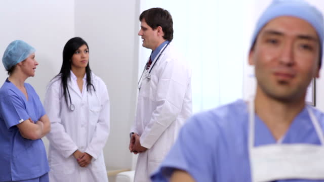 Portrait of surgeon with other medical personnel in background video