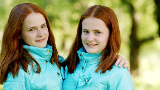 Portrait of teenage sisters twins. Two red-haired girls smiling, looking at the camera video