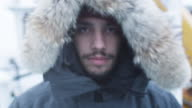 Portrait of the Adventurer in Warm Jacket with Fur Hood. It is Snowy and Windy video