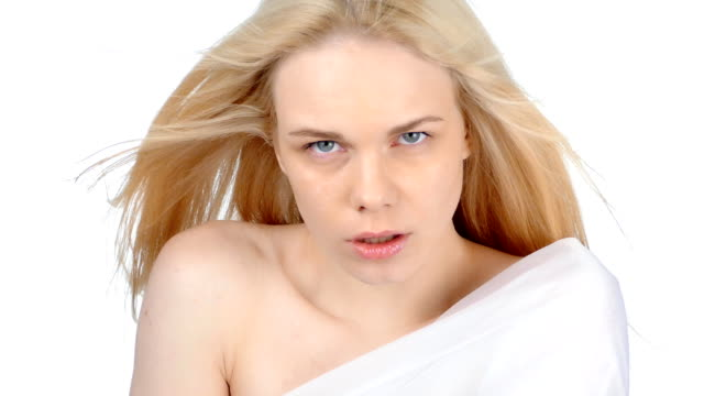 Portrait of the blonde in white clothes posing in the studio on a white background video