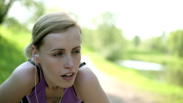 Portrait of tired athlete woman resting, close up video