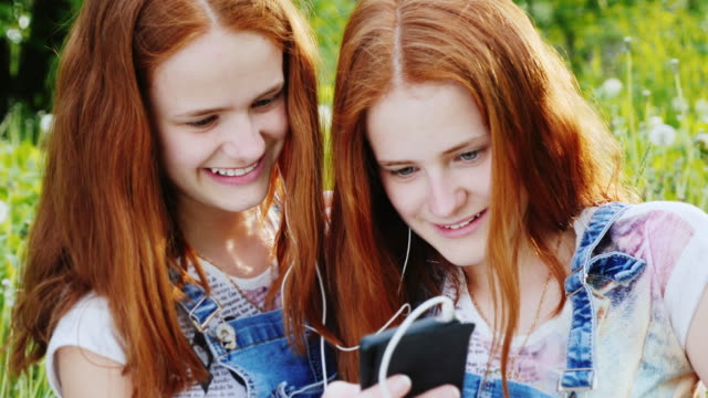 Portrait of two cute twin sisters with red hair. Together they look at the smartphone screen, rest on the nature video