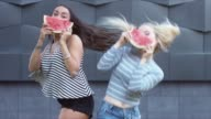 MED portrait of two young girls enjoying a watermelon in the street video