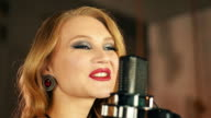 Portrait of vocalist with red lips make up perform at microphone. Retro style video