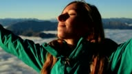 Portrait of woman arms outstretched on mountain top video