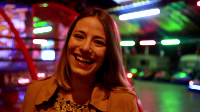 Portrait of woman looking at camera and laughing in amusement park video