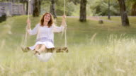 SLO MO DS Portrait of woman swinging in nature video