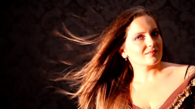 Portrait of woman turning head with hair fluttering in studio video