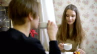 Portrait of young attractive brunette. Beautiful girl sitting in a cafe with my boyfriend and flirty talks with him. Patisserie, where coffee and cupcakes. Around of Christmas decoration video