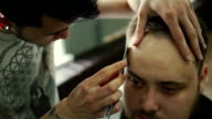 Portrait of young bald bearded man getting shaved with straight edge razor by hairdresser at barbershop video