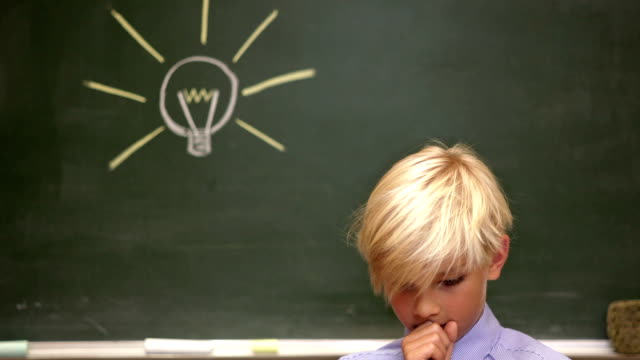 Portrait of young boy by the blackboard thinking of light idea video